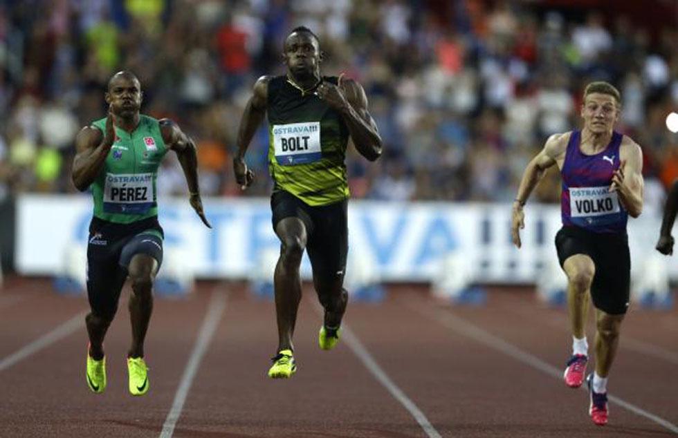 Yunier Pérez (izquierda) corrió codo a codo frente a Usain Bolt (centro).